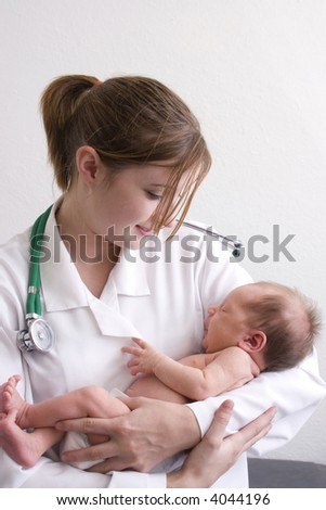 Smiling young doctor holding a beautiful newborn baby. - stock photo