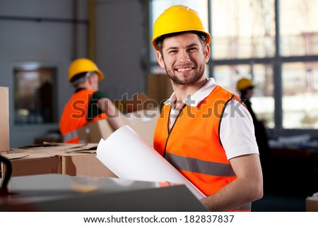 Smiling young factory worker is holding plans - stock photo