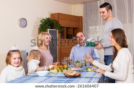 Smiling young family member receiving present from relatives at table - stock photo
