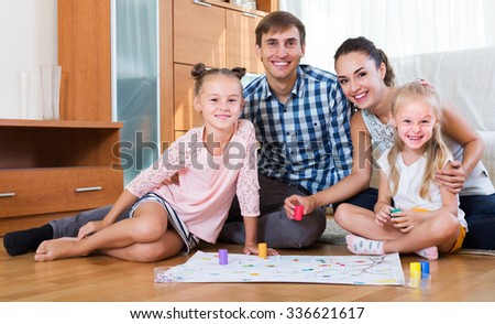 Smiling young family of four playing at board game in domestic interior - stock photo