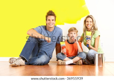 smiling young family painting interior wall of home. - stock photo