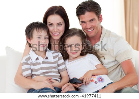 Smiling Young family watching TV on the sofa - stock photo