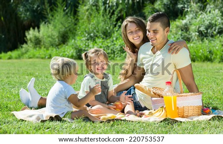 Smiling young family with little daughters having holiday with picnic at park. Focus on man  - stock photo