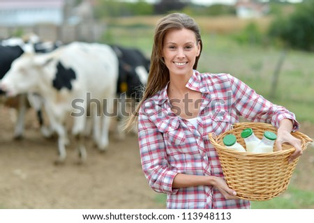Smiling young farmer carrying bottles of fresh milk - stock photo