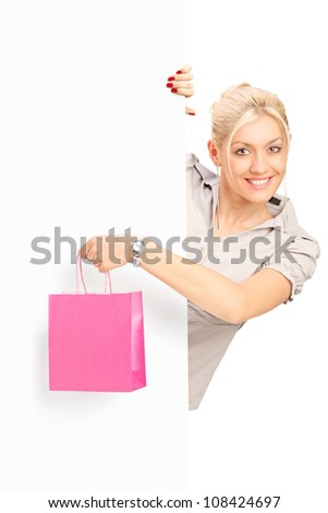 Smiling young female behind white panel holding a pink bag, isolated on white background - stock photo