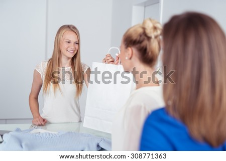 Smiling Young Female Cashier Giving a Shopping Bag to a Female Customer at the Counter Inside a Retail Fashion Store. - stock photo