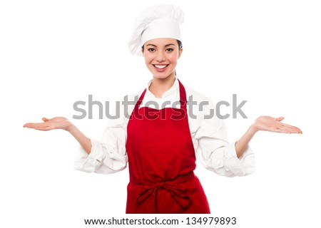 Smiling young female chef standing with open palms, warm welcome gesture. - stock photo