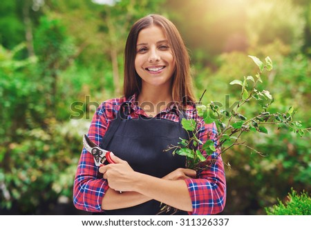 Smiling young female gardener pruning the plants standing in a lush green garden with a apir of secateurs in her hand smiling at the camera - stock photo