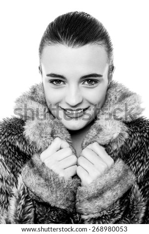 Smiling young female in warm fur jacket, black and white photo. - stock photo