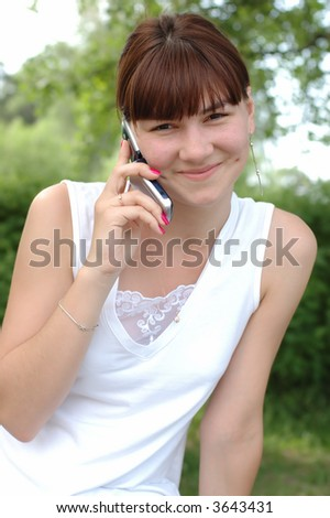 Smiling young female speaking on mobile phone - stock photo