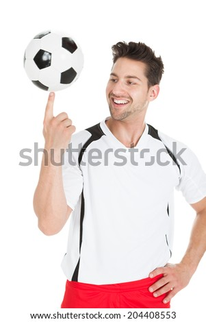 Smiling young football player spinning ball isolated over white background - stock photo