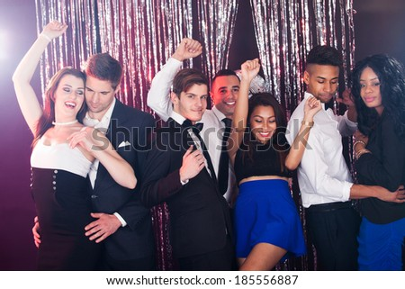 Smiling young friends dancing together at nightclub - stock photo