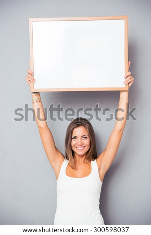 Smiling young girl holding blank board over gray background. Looking at camera - stock photo