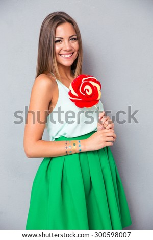 Smiling young girl holding lollipop on gray background. Looking at camera - stock photo