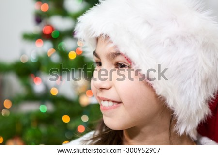 Smiling young girl in fur Santa hat, side view, copy space with Christmas tree light on background - stock photo