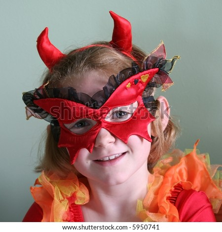 Smiling young girl in Satan costume and mask. - stock photo