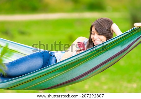 smiling young girl lying on a hammock looking at her cell phone - stock photo