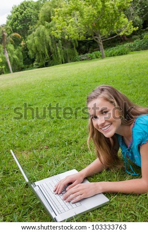 Smiling young girl lying on the grass in a public garden while working on her laptop - stock photo