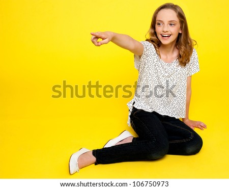 Smiling young girl pointing away. Sitting on floor - stock photo
