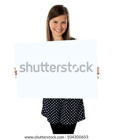 Smiling young girl showing blank placard to camera - stock photo