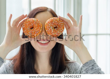 Smiling young girl taking sweets donuts on her eyes with window on the background. Shallow DOF. - stock photo