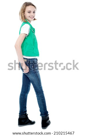 Smiling young girl turning back, hands in pocket - stock photo
