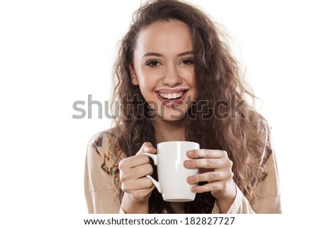 smiling young girl with a cup of milk on white background - stock photo