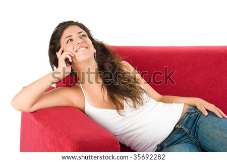 smiling young girl with cell phone sitting on the couch and speaking to friends - stock photo