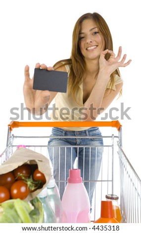 Smiling young girl with trolley. Holding credit card and looking at camera. White background, front view - stock photo