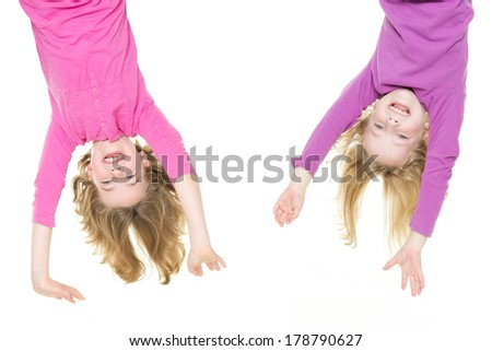 Smiling young girls hanging in front of white background - stock photo