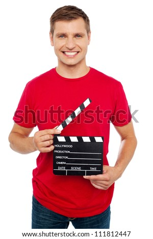 Smiling young guy holding clapperboard. The scene is about to take place - stock photo