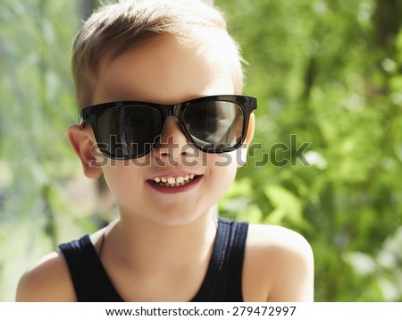 smiling young handsome boy in sunglasses.Outdoor fashion child - stock photo