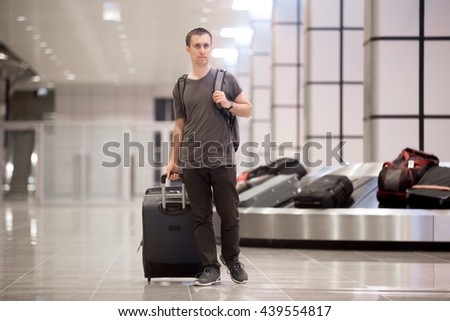 Smiling young handsome man passenger in his 20s leaving arrivals lounge of airport terminal building after collecting his luggage at conveyor belt - stock photo