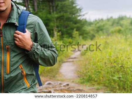 Smiling young hiker man with backpack walking in summer forest, copy-space in right part of image - stock photo