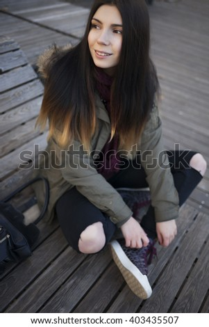 Smiling young hipster girl in grey parka coat and marsala scarf posing outdoors at day. Attractive young model and trendy youth fashion. Friendly smile, positive facial expression. - stock photo