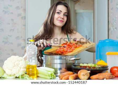 Smiling young housewife cooking veggie lunch with vegetables at her kitchen  at home - stock photo