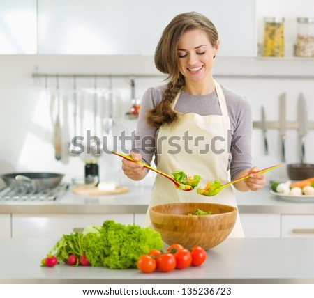 Smiling young housewife mixing fresh salad - stock photo
