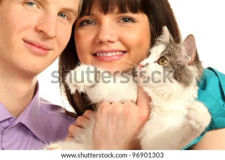 Smiling young husband and wife hold cat isolated on white background; focus on cat - stock photo