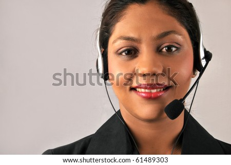 Smiling young Indian woman customer care assistant at call center - stock photo