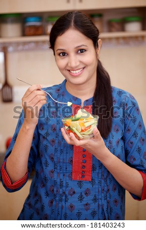 Smiling young Indian woman eating vegetable salad - stock photo