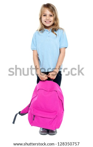 Smiling young kid facing camera while holding pink backpack. Education concept. - stock photo
