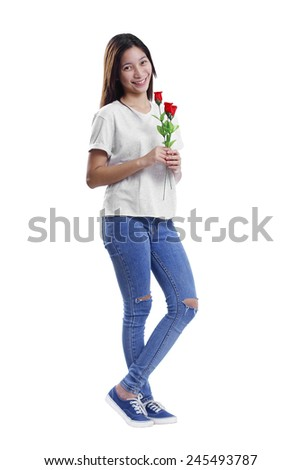Smiling young lady in casual outfit standing on a white background holding some red roses. Valentines day concept. - stock photo