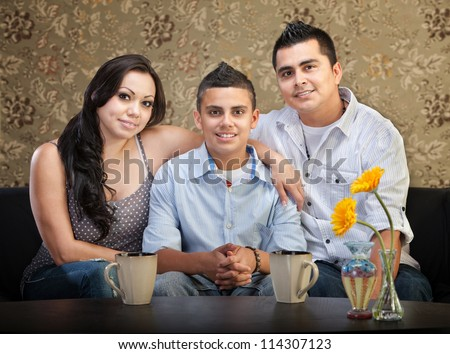Smiling young Latino family of three sitting together - stock photo