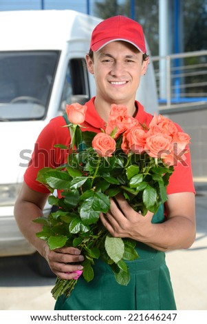 Smiling young male delivery courier man in front of cargo van delivering flowers - stock photo