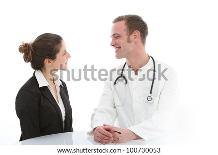 Smiling young male doctor seated at a table giving good news to his female patient during a consultation - stock photo