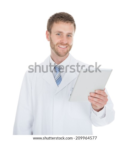 Smiling young male doctor using digital tablet over white background - stock photo
