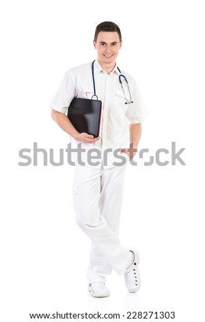 Smiling young male nurse posing and holding laptop under his arm. Full length studio shot isolated on white. - stock photo