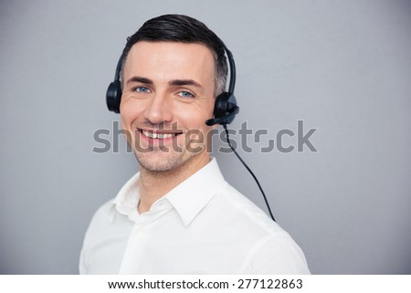Smiling young male operator in headphones looking at camera over gray background - stock photo