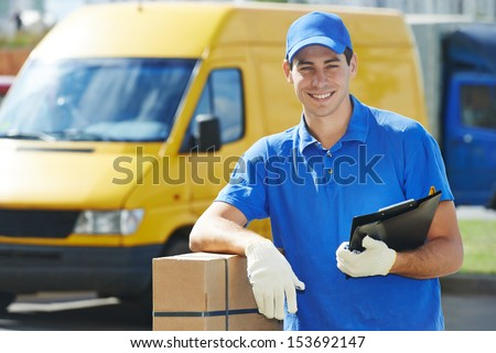 Smiling young male postal delivery courier man in front of cargo van delivering package - stock photo