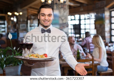Smiling young male waiter serving restaurant guests at table